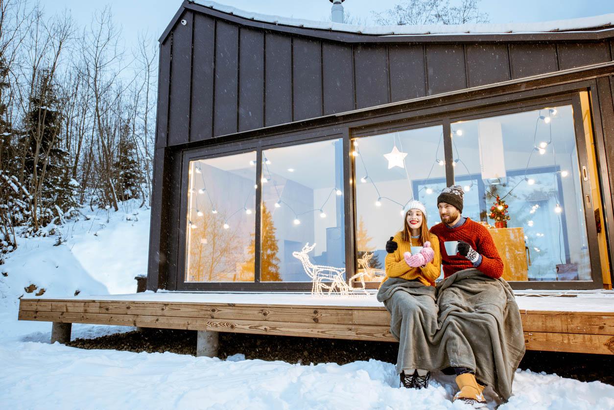 Couple réchauffe près de la maison pendant les vacances d'hiver