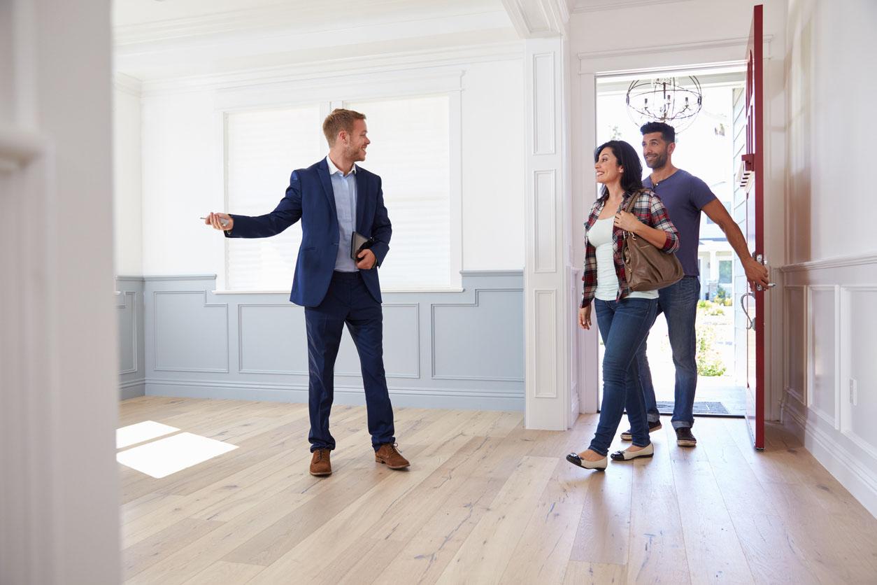 agent immobilier montre maison à un couple